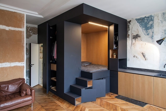 black box, serving as wardrobe and bed, minimalist living room, wooden floor, leather sofa