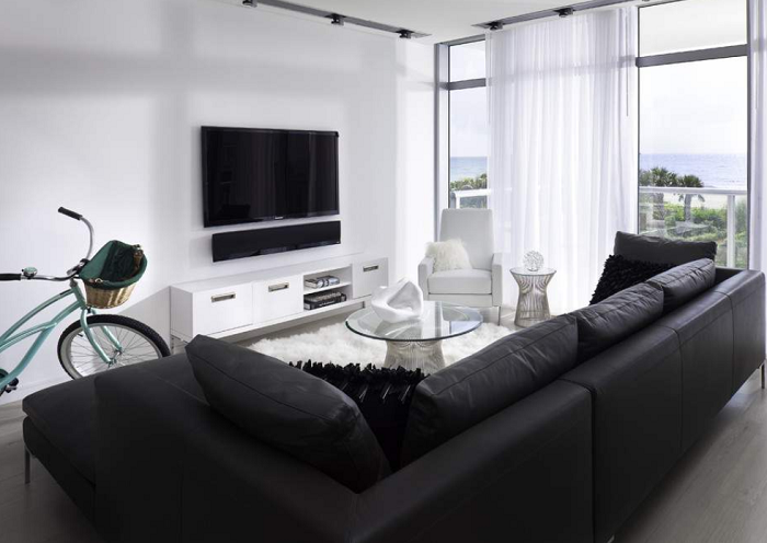 black leather sofa, white cabinet and armchair, glass coffee table, minimalist living room