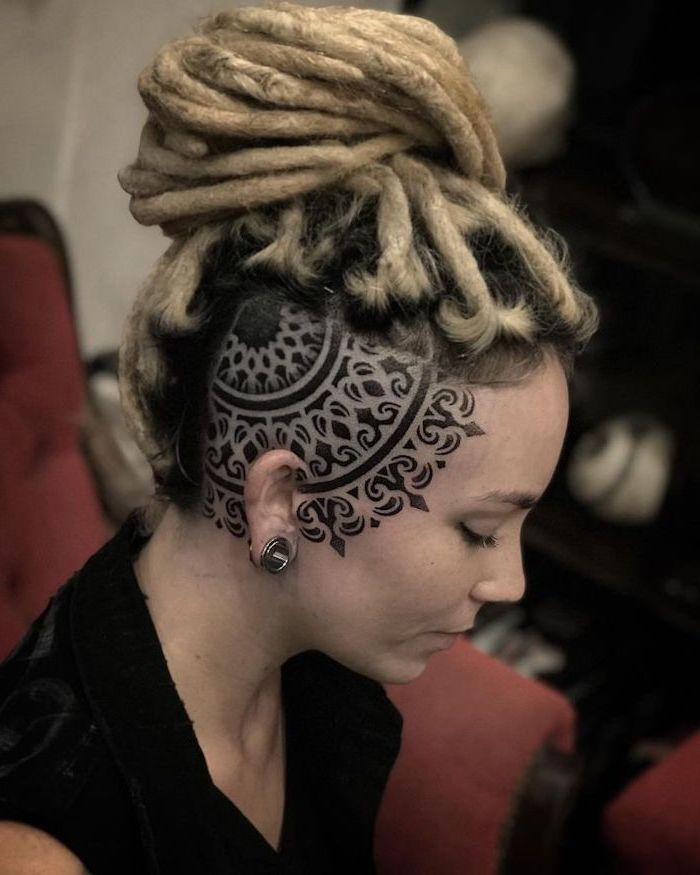 half shaved head, head tattoo, mandala flower tattoo, black top, blonde hair