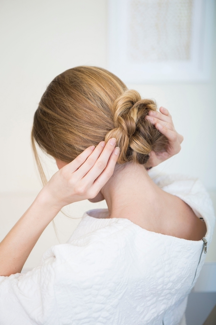 woman wearing a white top, blonde hair, in a braided bun, low updo, woman fixing her hair, beautiful hairstyles