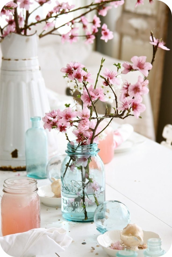 blossoming tree branches, blue mason jar, large white vase, table setting images, wooden white table