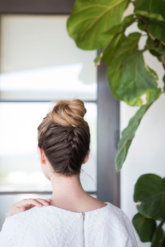 braid ending in a bun, brown hair, with blonde highlights, braid hairstyles for girls, woman wearing a white top