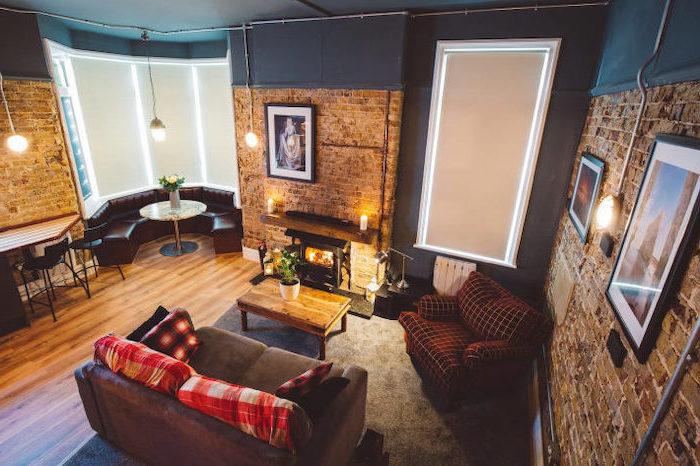 room design ideas, half brick, half blue walls, grey sofa, leather round sofa, wooden coffee table, industrial style