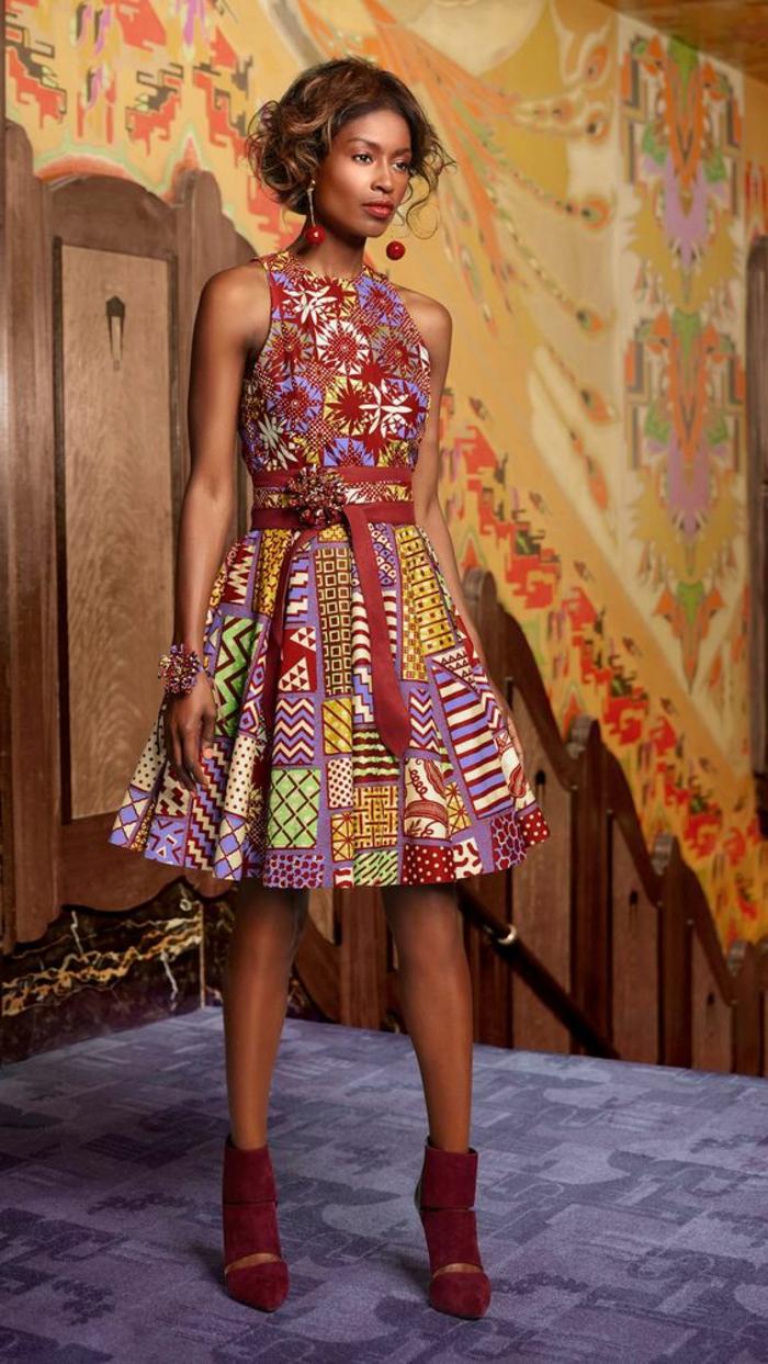 woman wearing burgundy heels, short dress, african print, standing on a purple carpet, red belt