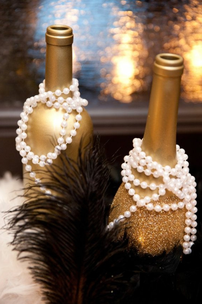 champagne bottles, painted in gold, decorated with pearls, black feathers, dining table centerpiece ideas