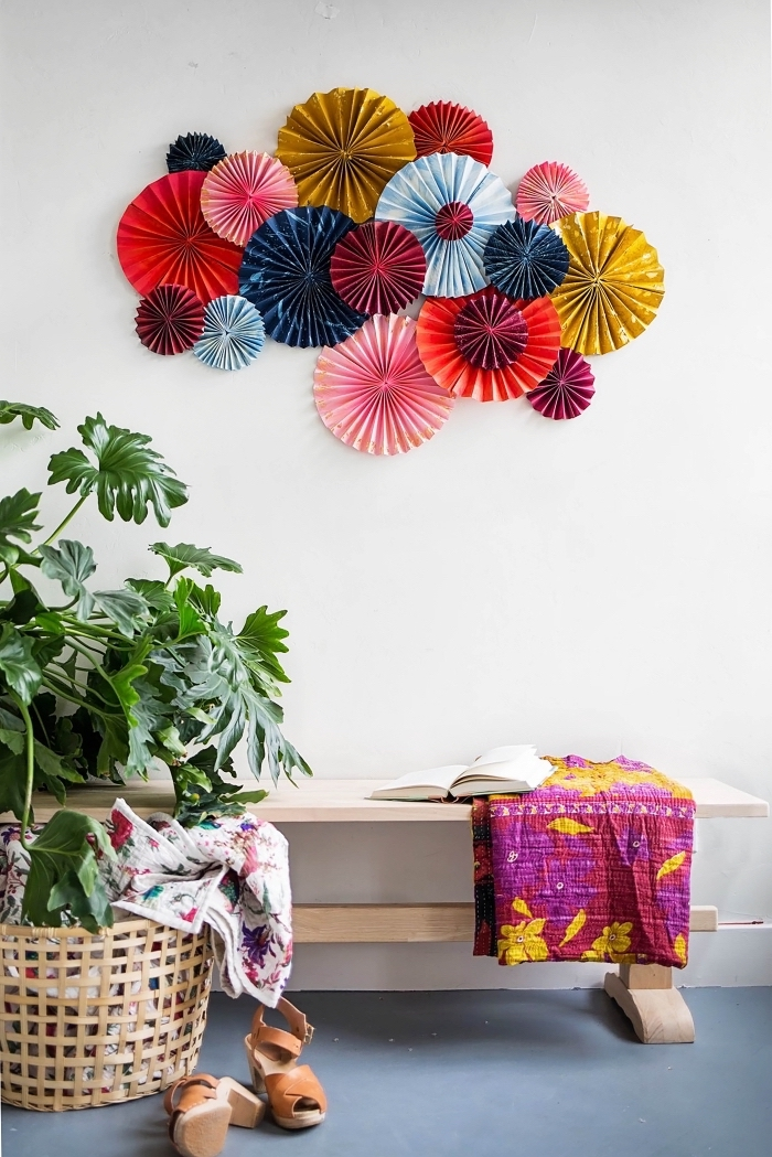 colourful paper fans, arranged together, over a wooden bench, girl room decor ideas, blue floor