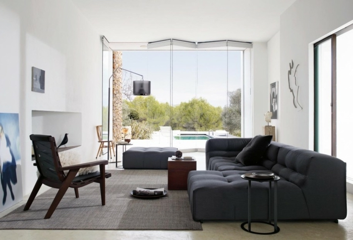 grey corner sofa and ottoman, black leather armchair, best color for living room walls, tall ceiling, grey carpet