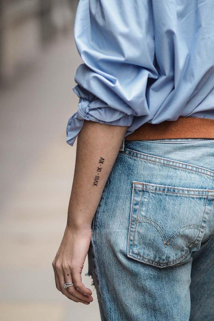 blue shirt and jeans, side arm tattoo, roman numeral tattoo ideas