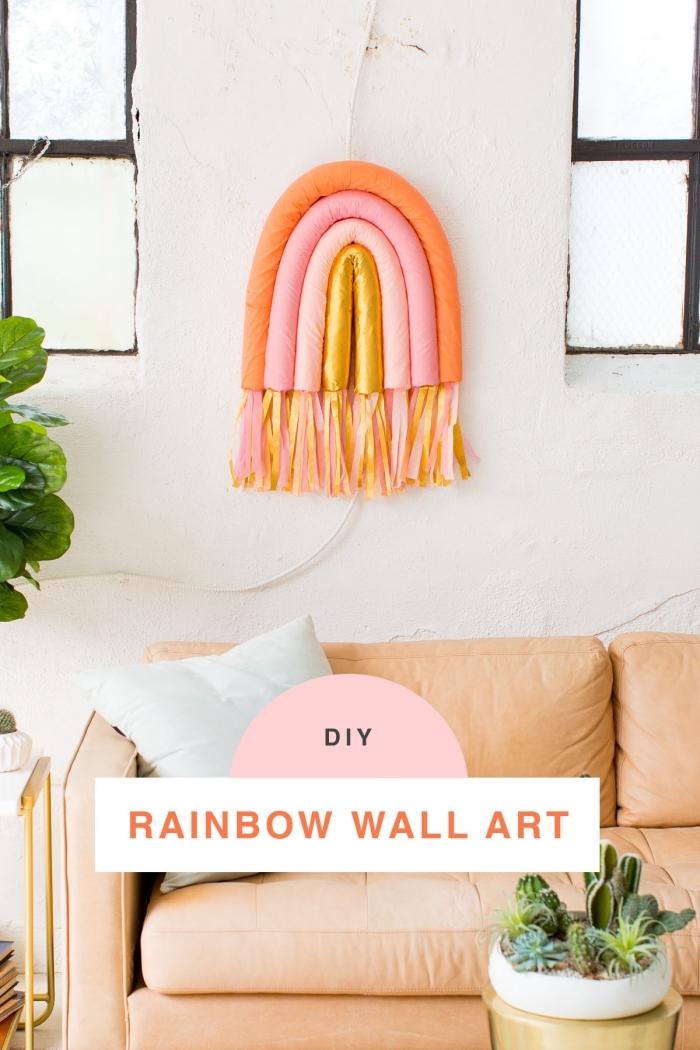 diy rainbow wall art, living room wall decor ideas, orange sofa, light blue throw pillows, white wall