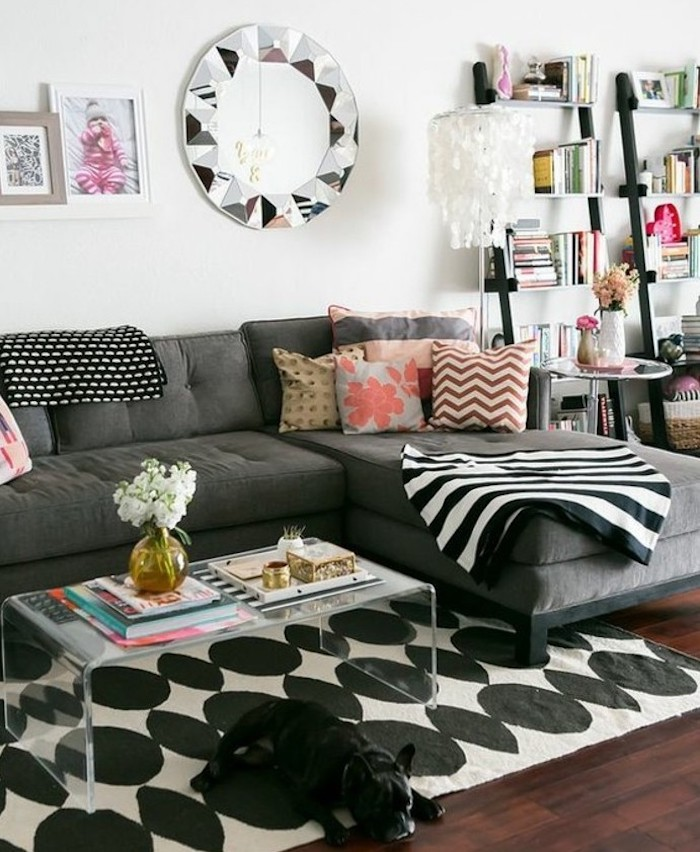light gray walls, grey corner sofa, colourful printed, throw pillows, wooden bookshelves, glass coffee table