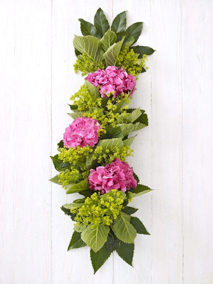 floral table runner, pink hydrangeas, green leaves, dining table centerpieces, wooden background