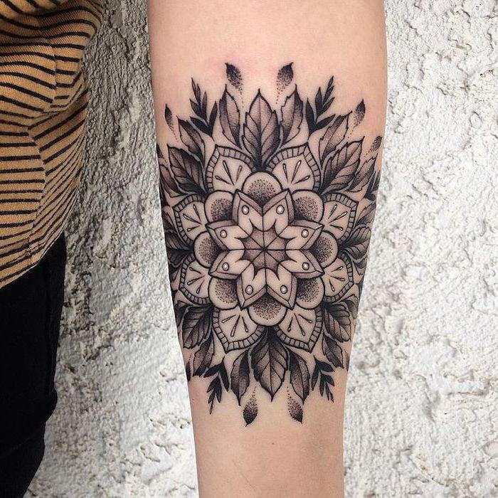 white background, forearm tattoo, lotus mandala tattoo, black pants, yellow and black, striped shirt