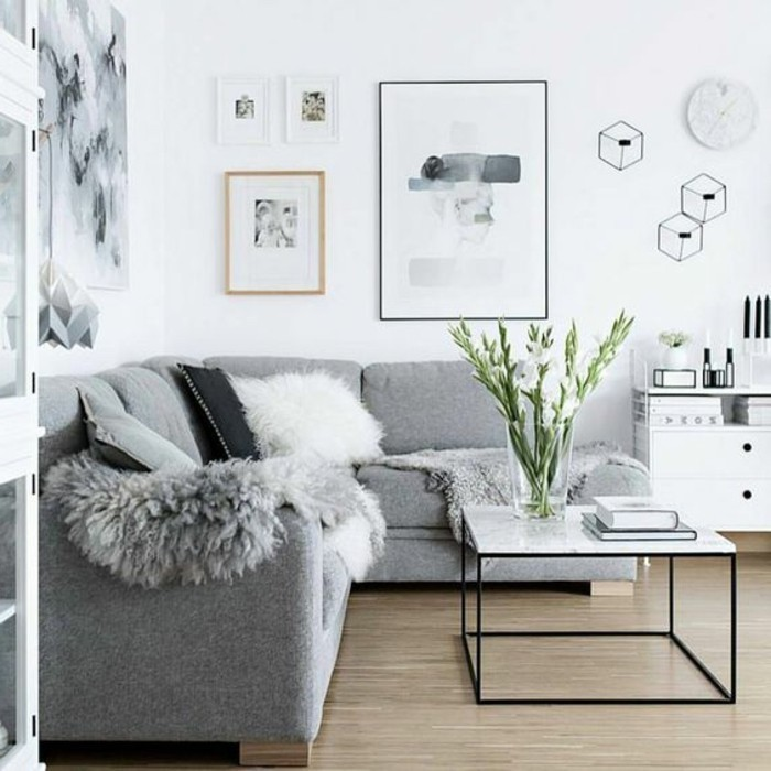marble coffee table, grey corner sofa, light gray walls, framed hanging art, large glass vase