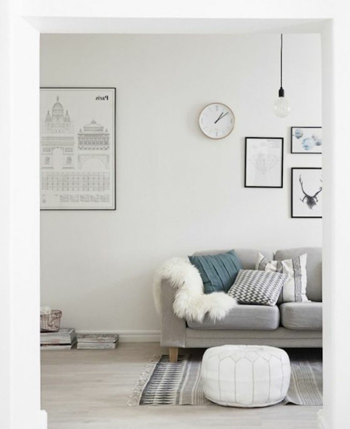 white ottoman, grey sofa, light gray walls, framed hanging art, blue throw pillow, yellow furry blanket