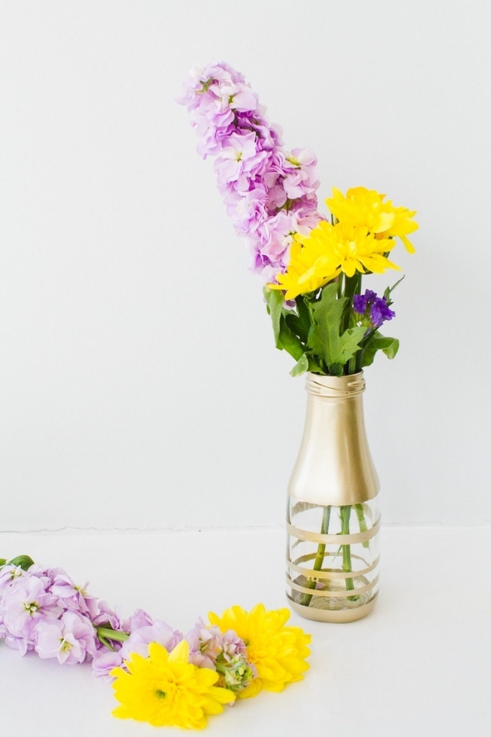 white background, dining room centerpieces, glass bottle, painted in gold, flower bouquets