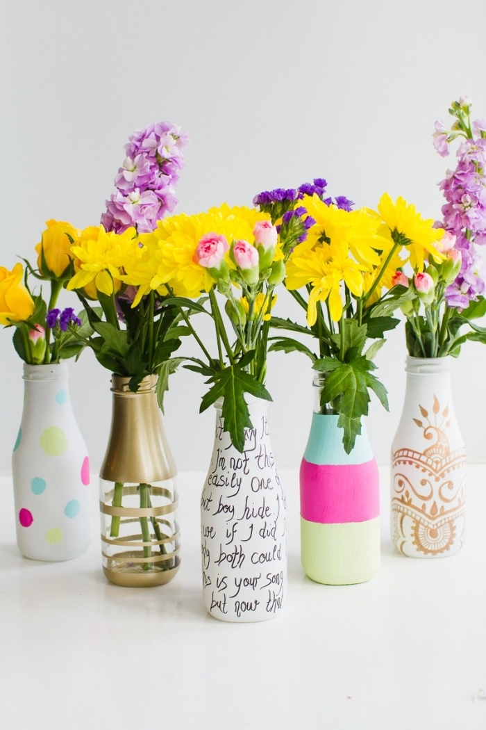 glass bottles, painted in different colours, kitchen table centerpieces, white background, flower bouquets