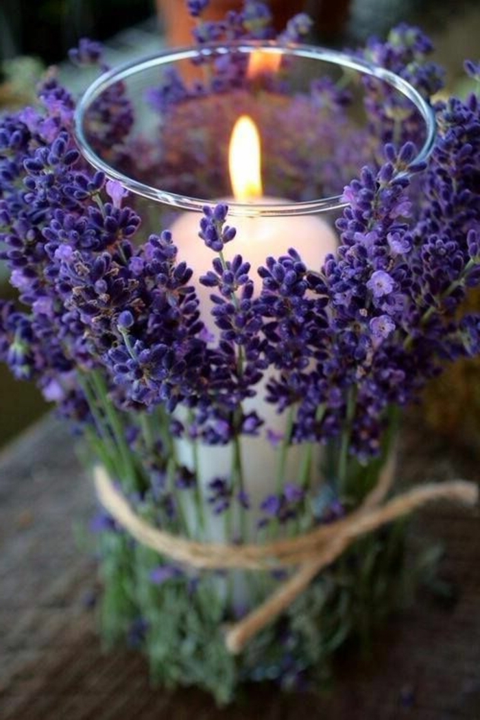 candle inside a glass, covered in lavender, wooden table, kitchen table decor, rustic style