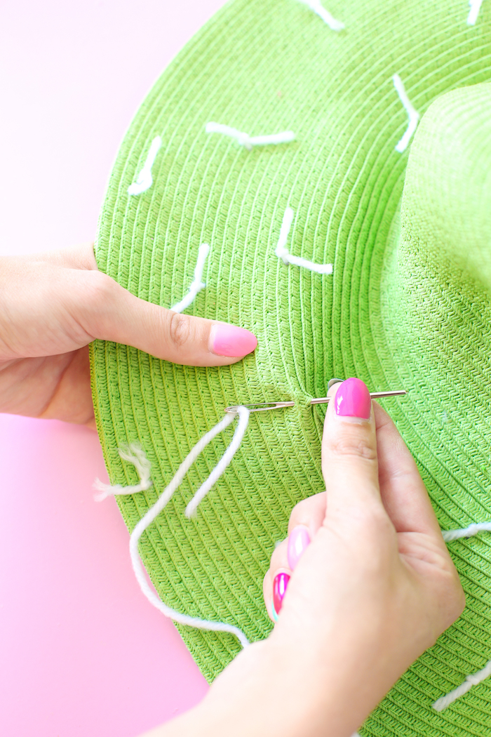 green hat, white yarn and a needle, pink nail polish, diy anniversary for him, pink background