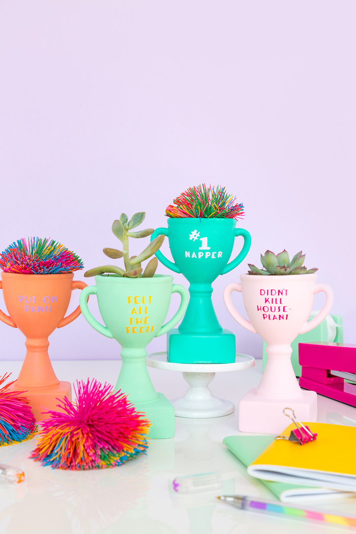 colourful trophies, unique gifts for boyfriend, colourful pom poms, white cake stand, purple background