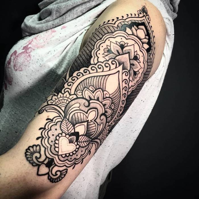 grey top, black background, mandala symbols, shoulder tattoo