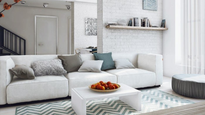 small white coffee table, gray living room walls, white brick wall, white sofa, blue and beige throw pillows