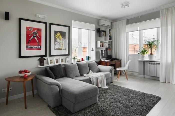 grey corner sofa, framed hanging posters, wooden side table, grey carpet, wooden floor, gray living room walls