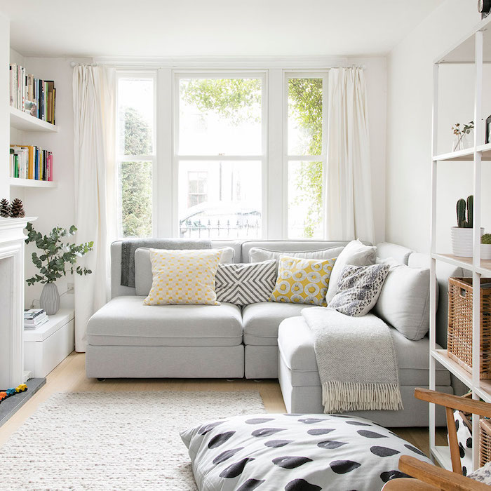 white corner sofa, wooden floor, white rug, white walls and curtains, how to decorate a small living room