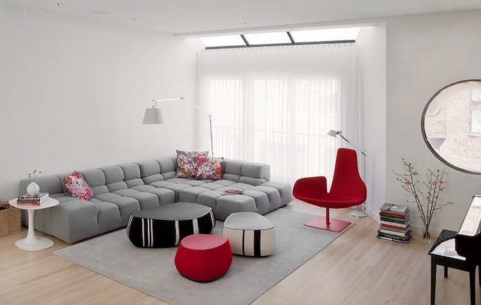 grey corner sofa, grey rug, red armchair, how to decorate a living room, red black and white ottomans