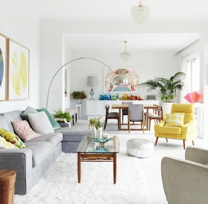 white walls, grey color schemes, grey sofa, yellow armchair, glass coffee table, white carpet