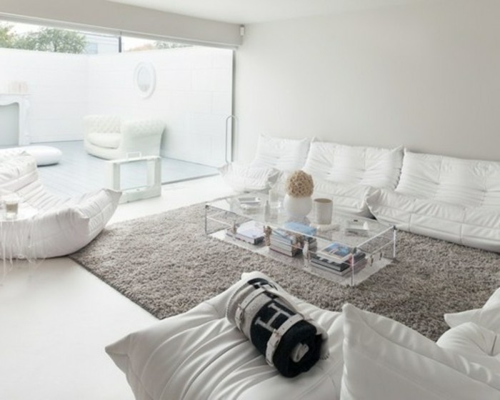 white sofas and armchair, glass coffee table, grey color schemes, large grey carpet, large window