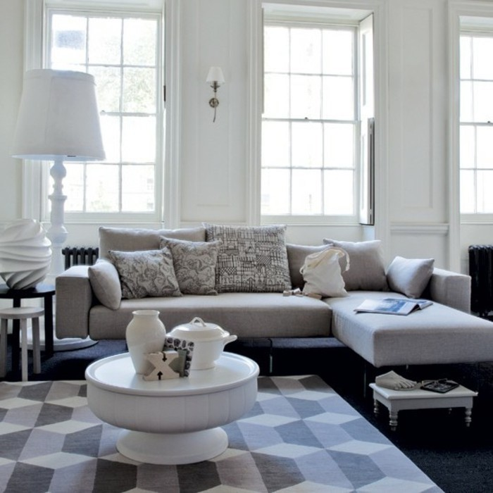 grey and white geometrical carpet, grey color schemes, grey corner sofa, printed throw pillows, white coffee table
