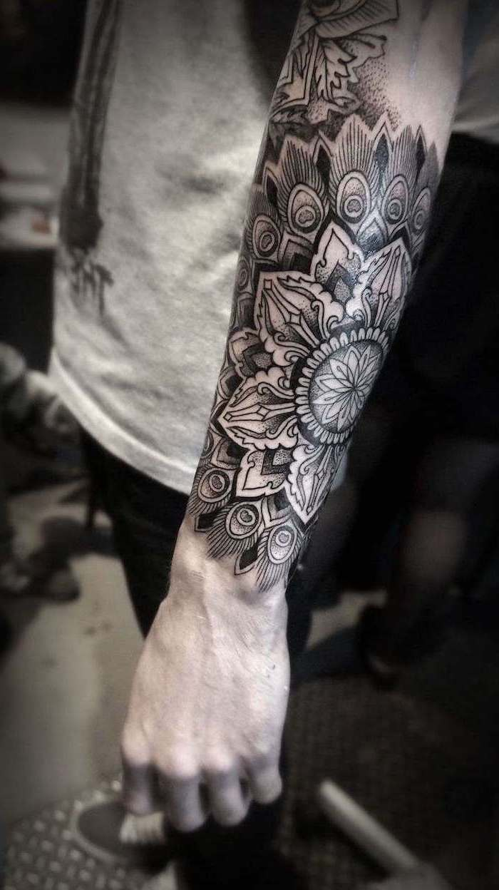 forearm tattoo, man wearing, grey top, black jeans, mandala symbols