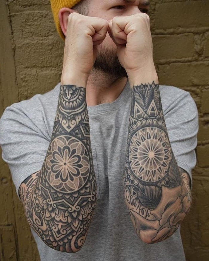 man wearing a yellow beanie, grey t shirt, sleeve tattoos, mandala meaning, brick wall