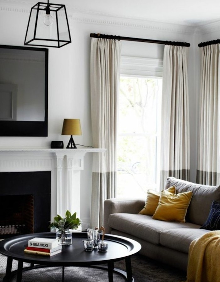 tv above the fireplace, grey living room walls, black metal coffee table, grey sofa, yellow throw pillows