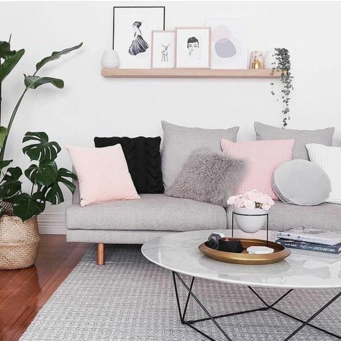 grey sofa, pink throw pillows, marble coffee table, wooden hanging shelf, grey living room walls