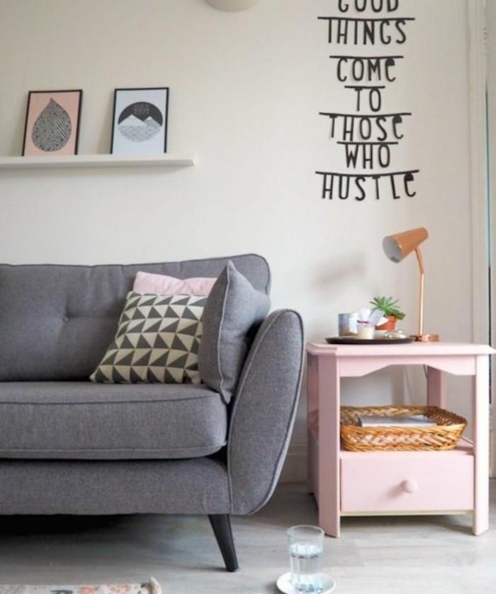 grey sofa, printed throw pillows, pink side table, grey living room walls, hanging shelf, framed art