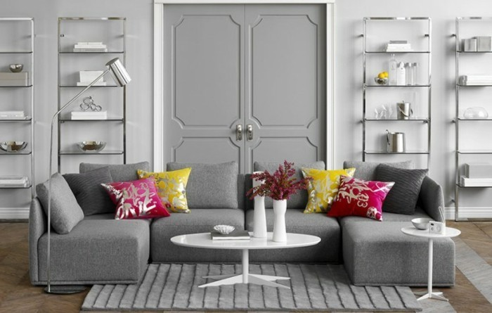 grey living room walls, grey corner sofa, pink and yellow, throw pillows, grey carpet, white coffee table