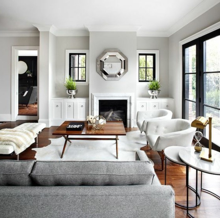 white armchairs, mirror above the fireplace, accent colors for gray, grey sofa, wooden coffee table