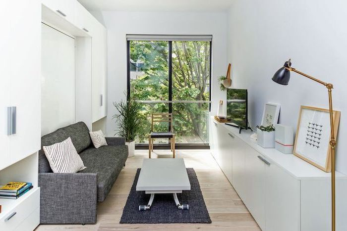grey sofa, living room furniture layout, small white coffee table, grey rug, white cabinets, wooden floor