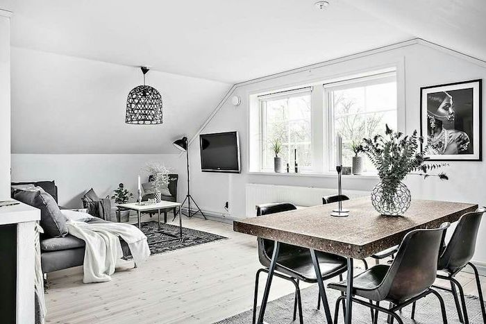 living room setup, grey sofa, metal black chairs, wooden floor, grey and black rug, small metal coffee table