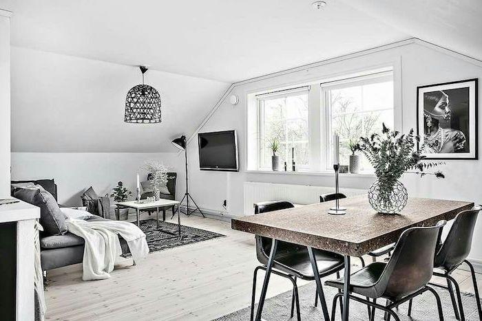 living room setup, grey sofa, metal black chairs, wooden floor, grey and black rug, small metal coffee table