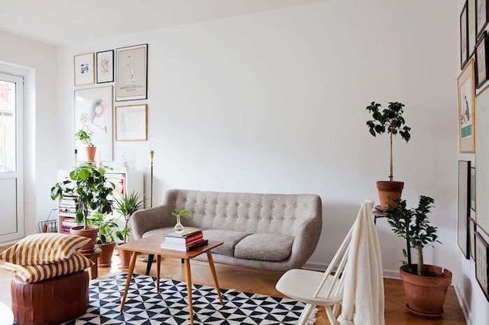 grey sofa, wooden coffee table, brown leather ottoman, living room setup, white chair, potted plants