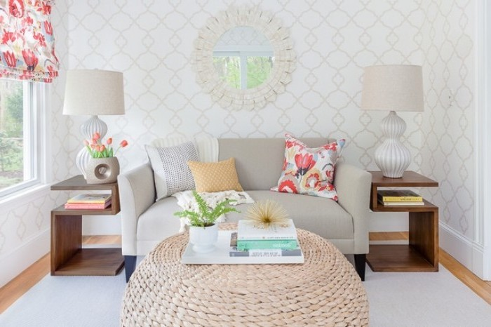 wooden ottoman, grey sofa, living room setup, white patterned walls, white rug, wooden floor, wooden side tables