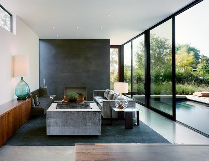 black accent wall, dark blue carpet, grey and black sofas, large tall windows, living room setup