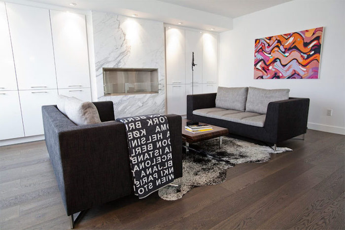 black and grey sofas, wooden floor, marble accent wall, living room setup, white cabinets