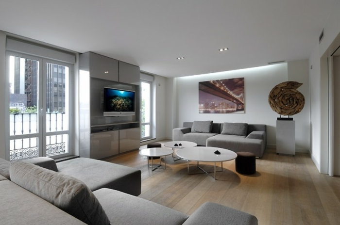 wooden floor, white round coffee tables, grey corner sofa, accent colors for gray, tall windows