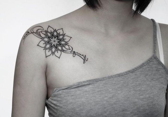grey top, mandala symbols, shoulder tattoo, short black hair, white background