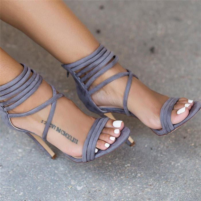 white nail polish, grey velvet shoes, date in roman numerals, foot tattoo