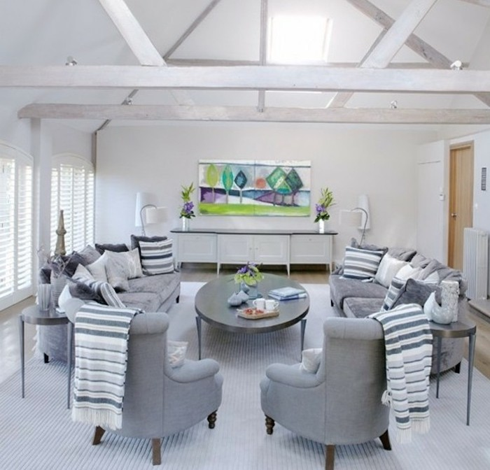 a shaped ceiling, grey armchairs, grey sofas, wooden table, colors that go with gray walls, abstract art