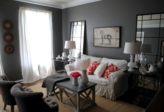 white sofa, colors that go with gray walls, red printed throw pillows, large mirrors, grey armchairs